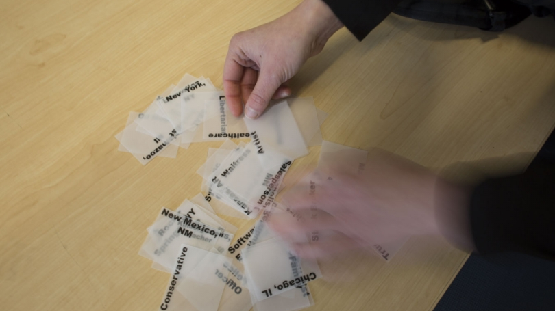 A person works with paper labels.